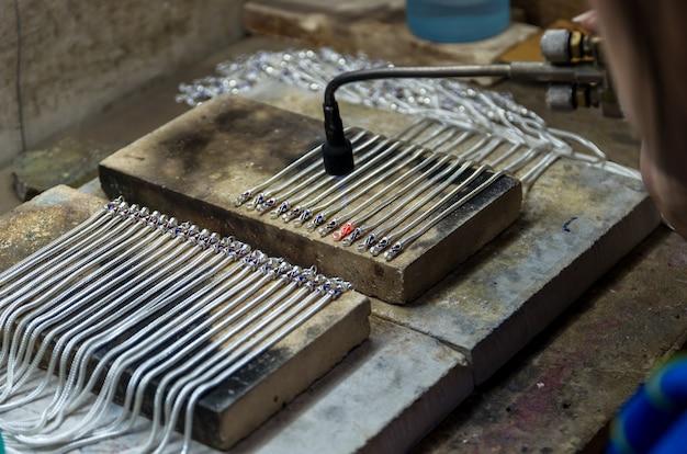 Gros Plan Du Bijoutier Artisanal Collier En Argent Avec Flamme. Photo Premium