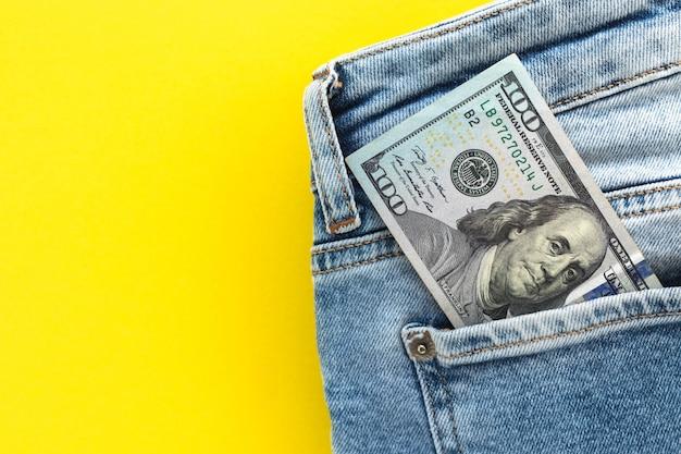 Gros plan du billet de 100 dollars qui sort de la poche du jean.