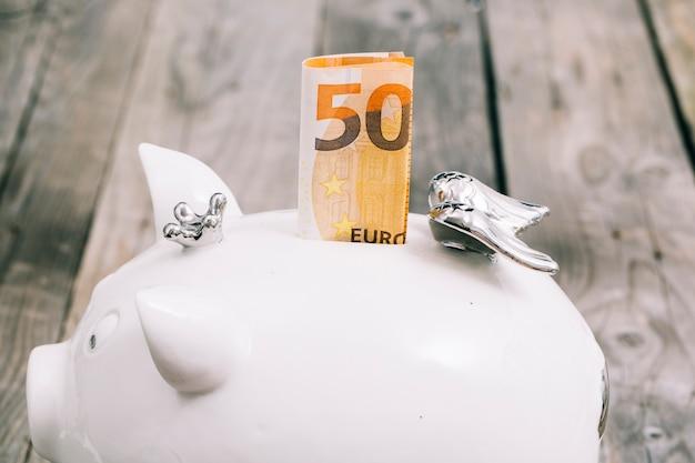 Gros plan du billet plié de cinquante euros dans la fente de la tirelire blanche