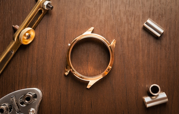 Gros plan du boîtier de montre en acier inoxydable doré brillant en attente de réparation, table d'horloger en bois vintage avec outil et équipement pour le concept de fond de service