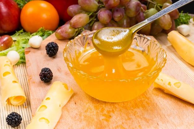 Gros plan du bol de conserves de fruits avec cuillère sur planche de bois avec du fromage et une variété de fruits frais