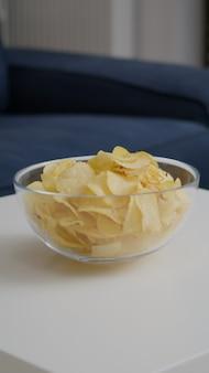Gros plan du bol de pommes de terre frites indésirables mis sur une table en bois dans une salle de fête vide