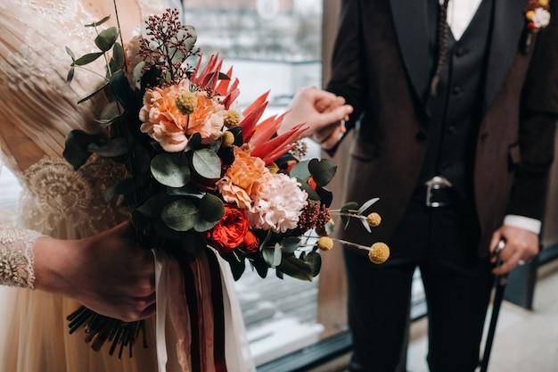 Gros plan du bouquet de mariage dans les mains de la mariée à côté du marié