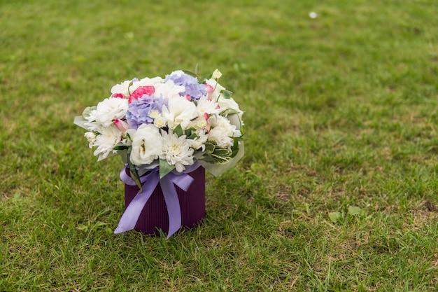 Gros plan du bouquet de mariée rose violet blanc sur fond d'herbe verte.