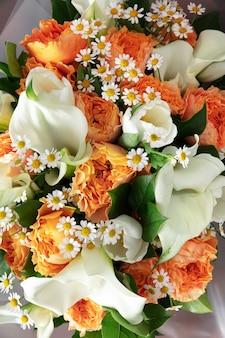 Gros plan du bouquet moderne de mode de différentes fleurs sur une surface en bois.