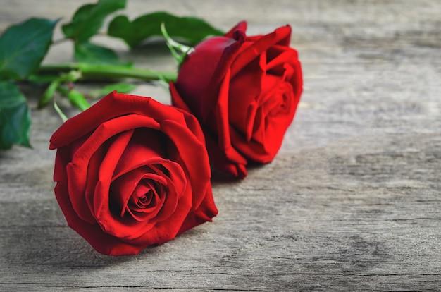 Gros plan du bouquet de roses rouges sur la vieille surface en bois