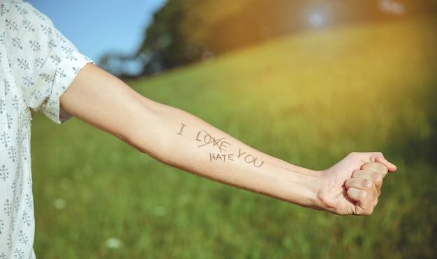 Gros plan du bras masculin avec le texte -je te déteste- et le mot -amour- barré dans la peau
