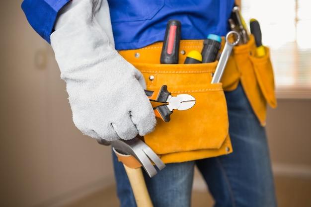 Gros plan du bricoleur dans la ceinture à outils