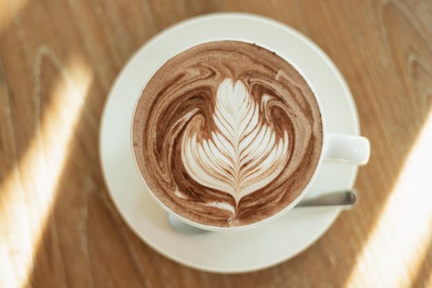 Gros plan du café chaud latte art sur table en bois