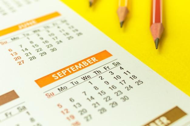 Gros plan du calendrier de septembre, arrière-plan concept de retour à l'école avec des crayons sur fond de table jaune