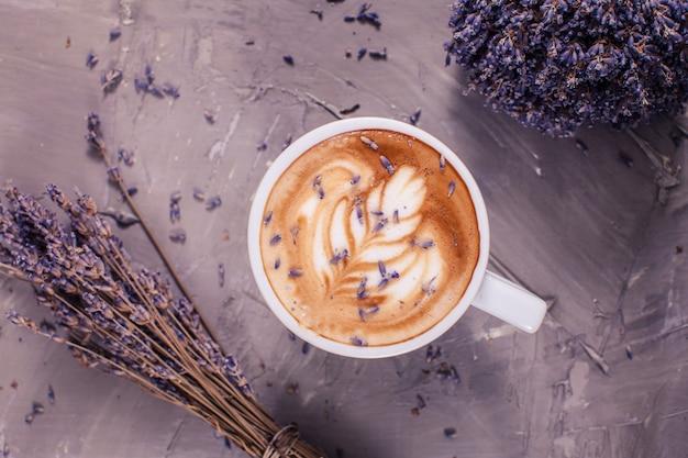 Gros plan du cappuccino lavande avec crème de la figure dans la tasse blanche