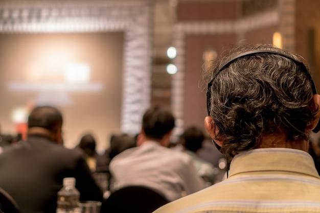 Gros plan du casque d'interprétation de la vue arrière du public qui porte et écoute les haut-parleurs