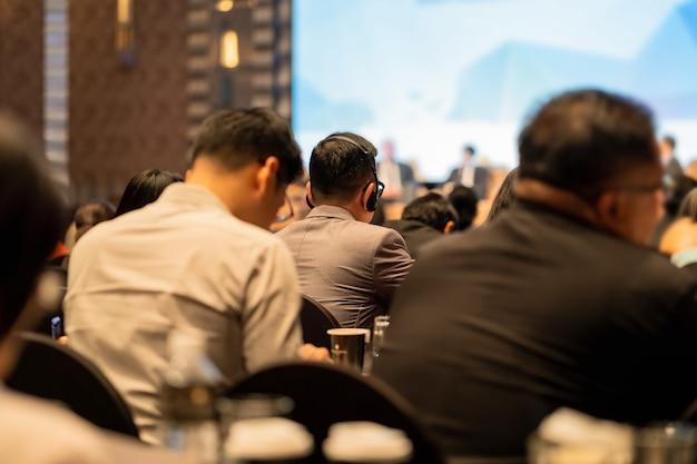 Gros plan du casque d'interprétation de la vue arrière du public qui porte et écoute