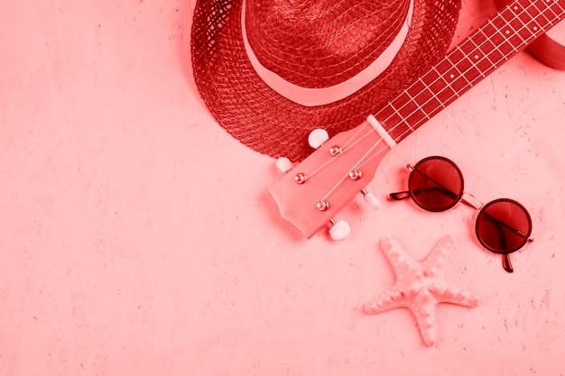 Gros plan du chapeau; un ukulélé; lunettes de soleil et étoile de mer sur fond texturé corail