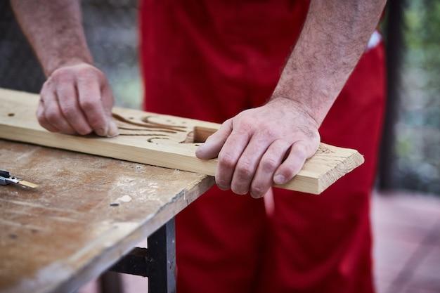 Gros plan du charpentier de mains mâle à l'aide de papier de verre pour poncer le détail en bois.