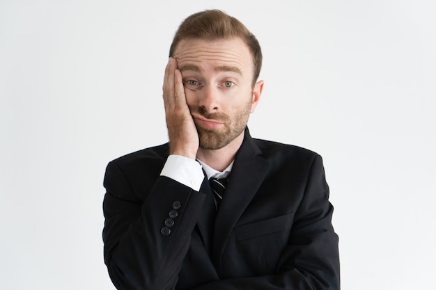 Gros plan du chef d'entreprise fatigué et ennuyé. jeune homme caucasien barbu en cravate et veste