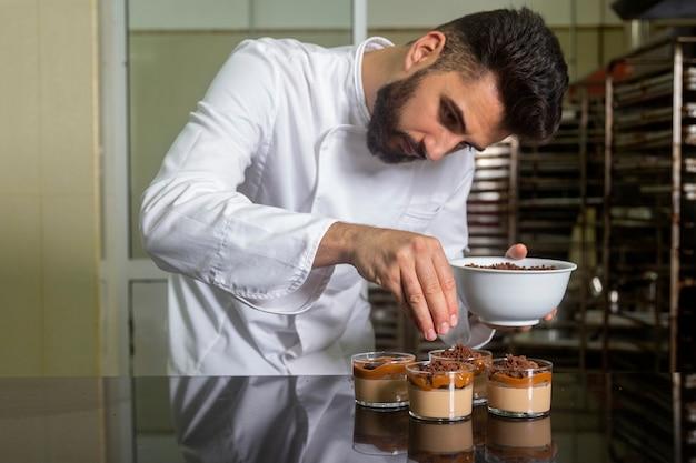 Gros plan du chef pâtissier avec masque travaillant la finition d'un dessert en verre.