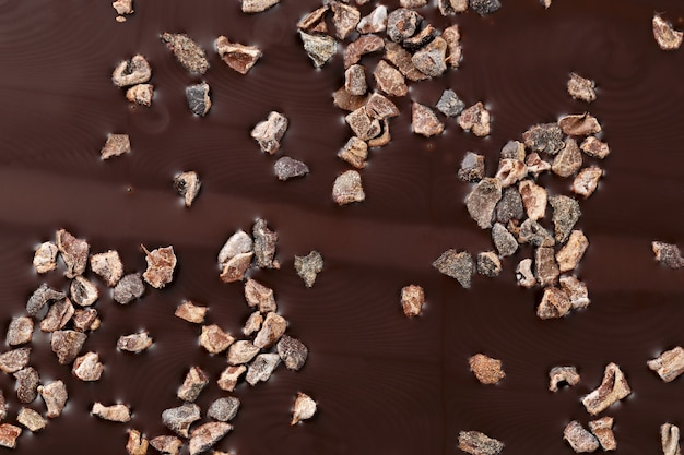 Gros plan du chocolat noir avec des morceaux de fèves de cacao