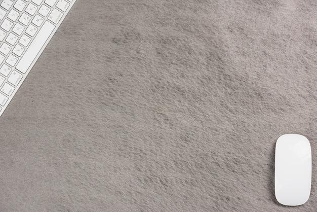 Gros plan du clavier et de la souris sans fil blancs au coin du fond gris