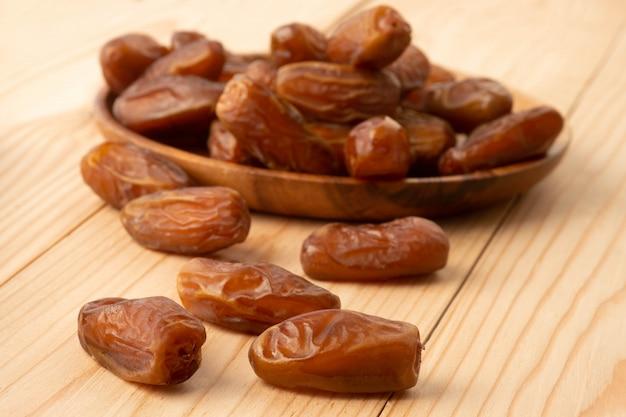 Gros plan du cluster dates plam. plam de dates fraîches sur table en bois.