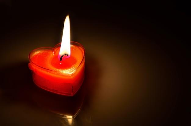 Gros plan du coeur de bougie rouge brûlant sur fond sombre