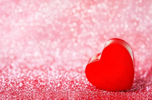 Gros plan du coeur rouge sur des paillettes rouges