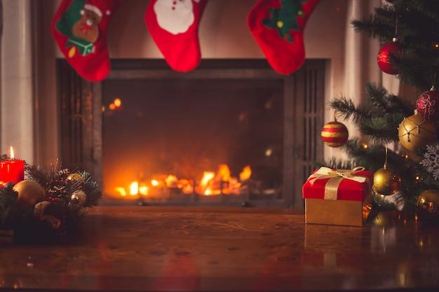 Gros plan du coffret cadeau de noël rouge avec ruban doré à côté de l'arbre de noël décoré et de la cheminée
