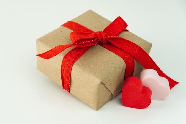 Gros plan du coffret cadeau avec ruban rouge et deux coeurs sur fond blanc