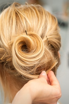 Gros plan du coiffeur féminin coiffant les cheveux blonds d'une jeune femme dans un salon de beauté