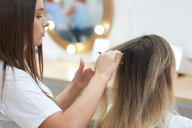 Gros plan du coiffeur en train de peigner les cheveux du client dans un salon de beauté
