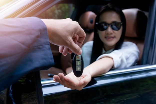 Gros plan du concessionnaire donnant la clé de la nouvelle voiture propriétaire. nouvelle voiture. concessionnaire automobile donnant clé automobile femme pour essai routier sur route de campagne.