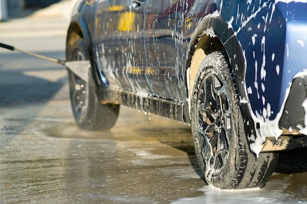 Gros plan du conducteur masculin lavant sa voiture avec un jet d'eau haute pression sans contact dans un lave-auto en libre-service.