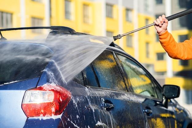 Gros plan du conducteur masculin lavant sa voiture avec un jet d'eau haute pression sans contact