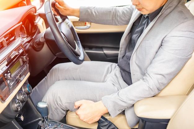 Gros plan du conducteur tirant le levier de frein à main dans la voiture