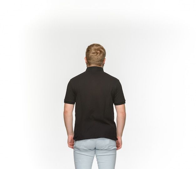Gros plan du corps du jeune homme en t-shirt noir vide isolé sur espace blanc. maquette pour concept de conception