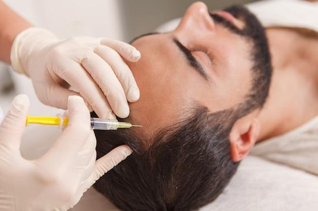 Gros plan du cosmétologue injectant des vitamines dans le cuir chevelu de l'homme chauve