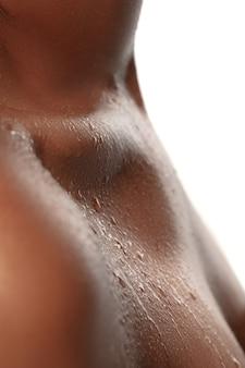 Gros plan du cou et de l'épaule féminins avec des gouttes d'eau dans un bel éclat. . beauté, mode, soins de la peau, concept de cosmétiques.