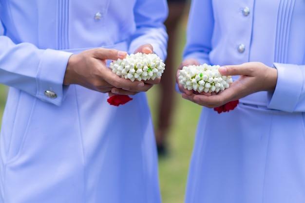 Gros plan du demi-corps d'une infirmière en blanc, tenant une guirlande de jasmin dans ses mains