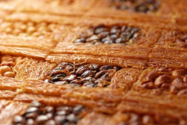 Gros plan du dessert turc au baklava avec du miel et des noix