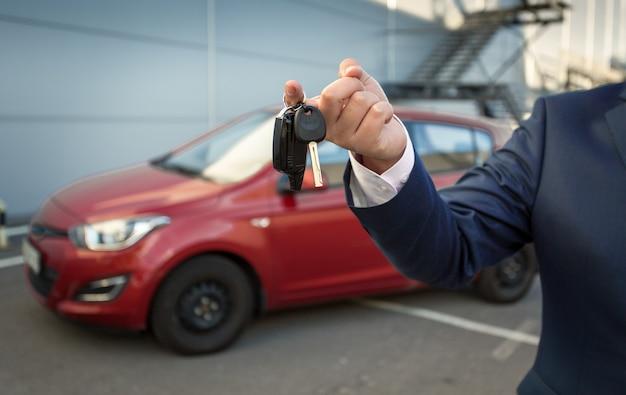 Gros plan du directeur des ventes tenant des clés de voiture contre une nouvelle voiture