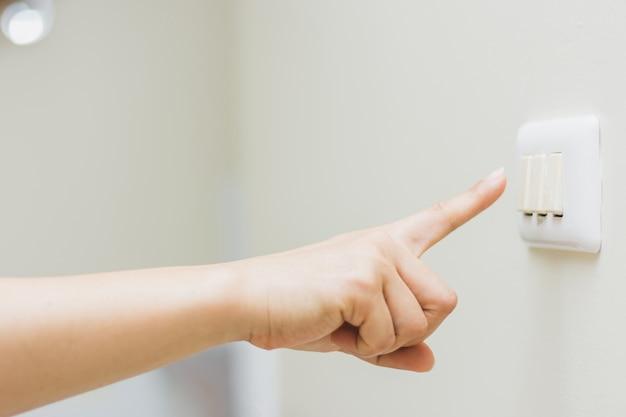 Gros plan du doigt de la femme s'allume ou s'éteint sur l'interrupteur d'éclairage
