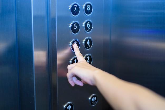 Gros plan du doigt humain pousse le bouton de l'ascenseur