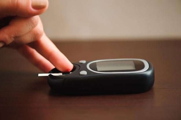 Gros plan du doigt masculin avec une goutte de sang et une bandelette de test pour vérifier le niveau de sucre dans le sang par glucomètre.