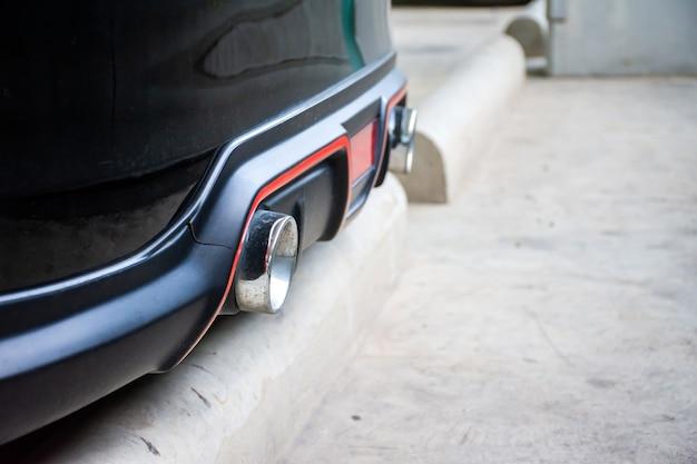 Gros plan du double tuyau d'échappement argenté sur une voiture noire.
