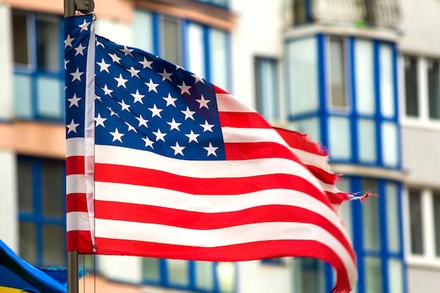 Gros plan du drapeau américain contre les toits de la ville