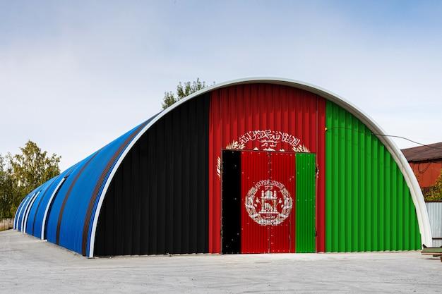 Gros plan du drapeau national afghan peint sur le mur de métal d'un grand entrepôt le territoire clos contre le ciel bleu. le concept de stockage de marchandises, entrée dans une zone fermée, logistique