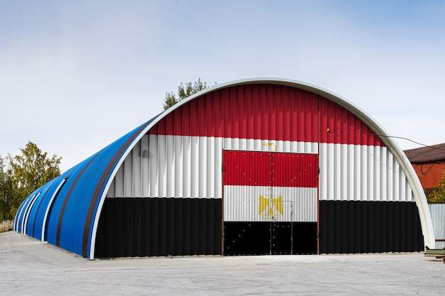Gros plan du drapeau national égyptien peint sur le mur de métal d'un grand entrepôt le territoire clos contre le ciel bleu. le concept de stockage de marchandises, entrée dans une zone fermée, logistique