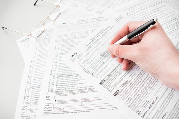 Gros plan du formulaire fiscal de remplissage comptable masculin. homme écrivant quelque chose assis à son bureau. remplir le formulaire de déclaration de revenus des particuliers 1040, faire le rapport financier, les finances de la maison ou le concept d'économie