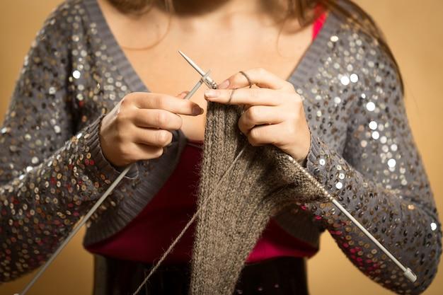 Gros plan du foulard en laine à tricoter femme avec des aiguilles