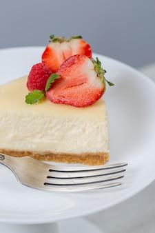 Gros plan du gâteau au fromage aux fraises sur une plaque blanche sur un stand de gâteau